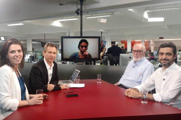 Sentados na mesa do estúdio da TV Folha, a repórter Thais Bilenky, o repórter especial Fernando Canzian e os colunistas Clóvis Rossi e Bruno Boghossian durante debate na TV Folha. Na tela da TV, a correspondente em Nova York, Danielle Brant.
