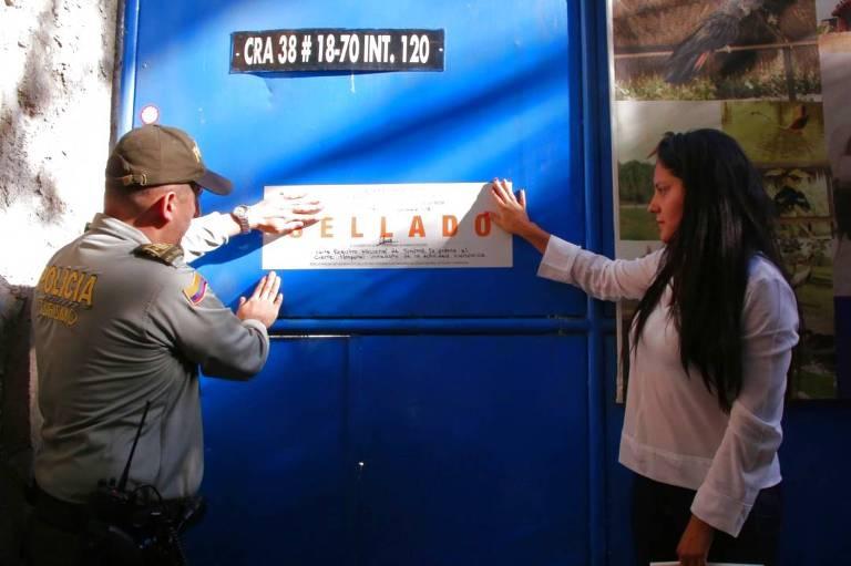 Agentes da prefeitura colocam selo de lacrado em portão azul do museu de Pablo Escobar