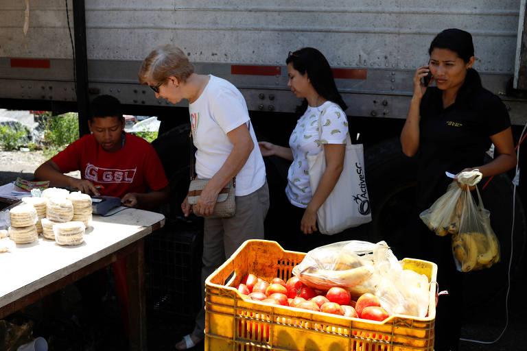 O feirante aparece sentado a uma mesa, enquanto três mulheres esperam em uma fila. `À frente delas aparece uma caixa de tomates.