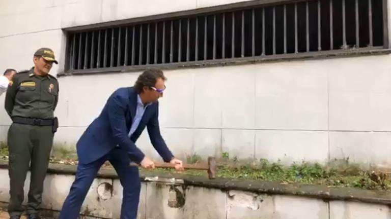 Gutiérrez usa uma marreta para quebrar parte de uma mureta do prédio