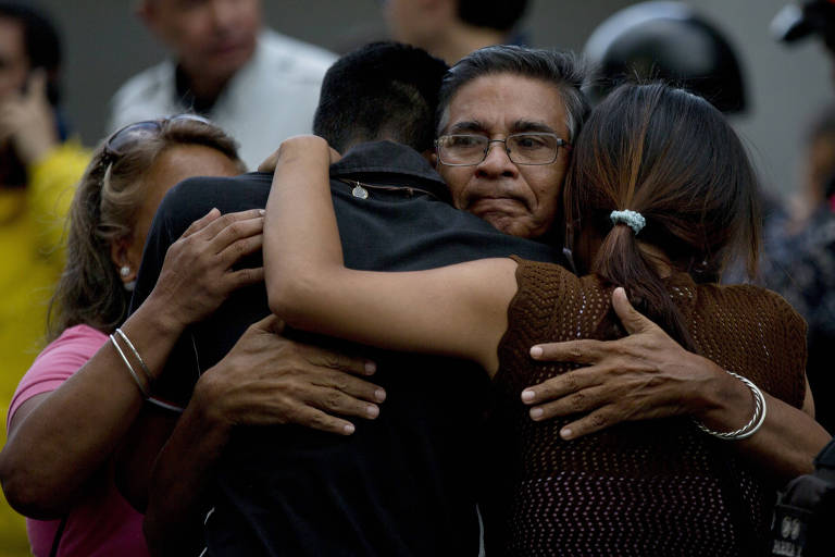 Amigos do vereador Fernando Albán se abraçam do lado de fora da prisão onde ele morreu, em Caracas