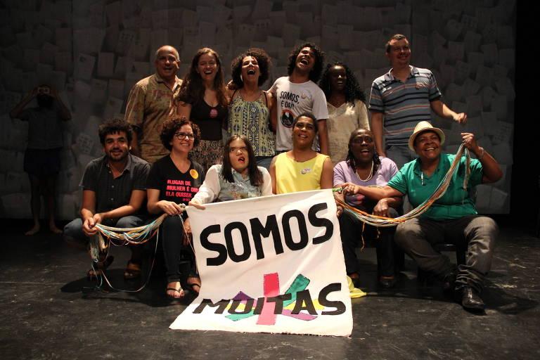 """Membros do coletivo Muitas, de Minas Gerais, que elegeu Áurea Carolina para a Câmara; na foto, estão sentados erguendo a faixa """"somos muitas"""""""
