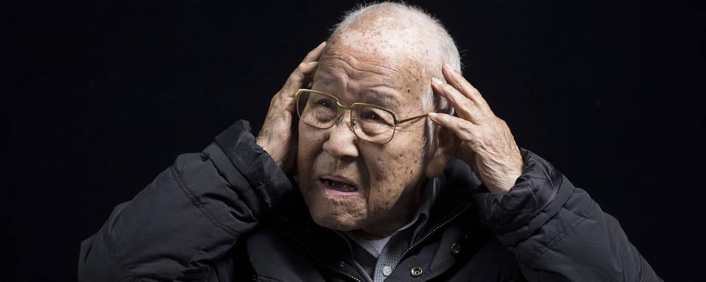 Takashi Morita, 94, com as mãos na cabeça