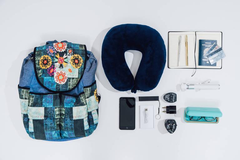Mochila, descanso para pescoço, carregador, celular, óculos e bloco de papel vistos de cima