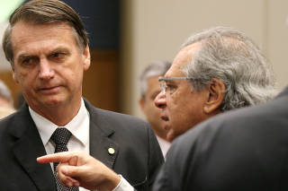 FILE PHOTO: Federal deputy Bolsonaro, a candidate for the Presidency of the Republic for the PSL, listens to economist Paulo Guedes before a lunch with businessmen at the FIRJAN headquarter in Rio de Janeiro