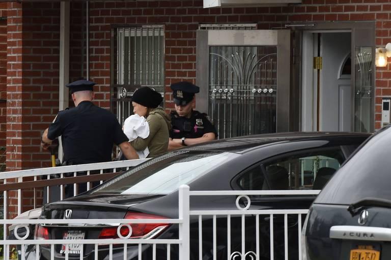 Dois policiais de farda preta são vistos ao lado de uma mulher de verde com um bebê no colo.