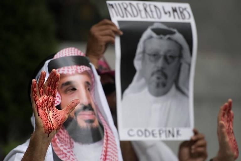 Manifestante vestido como o príncipe herdeiro da Arábia Saudita, Mohammed bin Salman, segura cartaz com o rosto de Jamal Khashoggidurante protesto em Washington contra o desaparecimento do jornalista