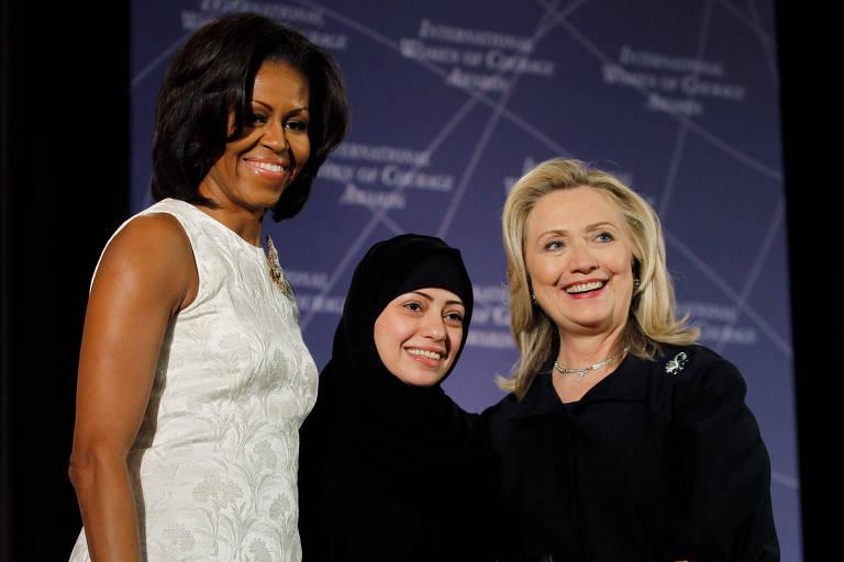 A ativista saudita Samar Badawi ao lado da ex-primeira dama dos EUA Michelle Obama (esq.) e da ex--secretária de estado Hillary Clinton; Samar foi presa por lutar pelos direitos humanos em seu país