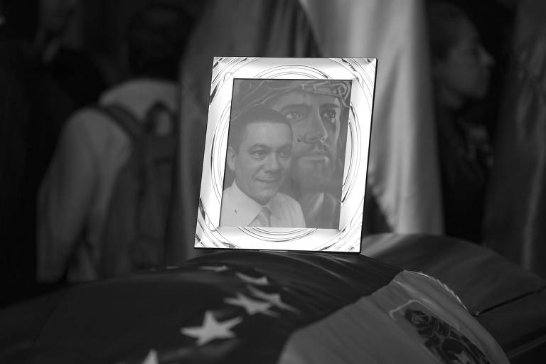Porta-retrato com imagem de Fernando Albán sobre o caixão com o corpo dele na Assembleia Nacional, em Caracas