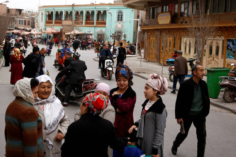 Seis mulheres aparecem conversando em uma rodinha, sendo que três delas usam o véu islâmico