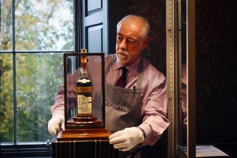 Homem mostra garrafa de uísque que será leiloada pela Sotheby's