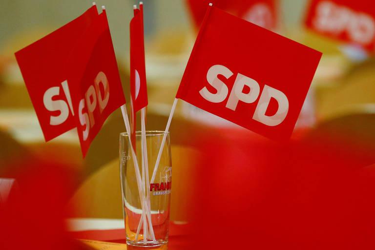 Quatro pequenas bandeiras vermelhas com a letra SPD são vistas dentro de um copo sobre uma mesa em close