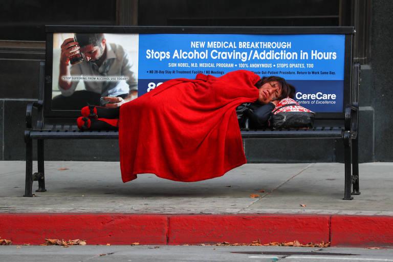 Pessoa dorme em banco na calçada, coberta por cobertor vermelho, no qual há cartaz sobre prevenção à dependência química
