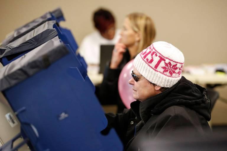 Duas mulheres estão diante das urnas, que têm paredes azuis. Ao fundo há outra observando o sufrágio.