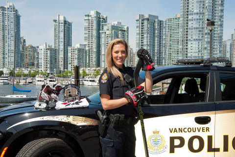 In a photo provided by the Vancouver Police Department, Meghan Agosta in her police uniform and wearing her hockey gloves. With a full-time job at the Vancouver Police Department, Agosta could easily have decided to retire from hockey this year, but remains determined to return for her fifth Winter Olympics, in Beijing in 2022. (Vancouver Police Department via The New York Times) -- NO SALES; FOR EDITORIAL USE ONLY WITH NYT STORY HKW CANADA OFFICER BY LUCAS AYKROYD FOR OCT. 14, 2018. ALL OTHER USE PROHIBITED. -- ORG XMIT: XNYT256