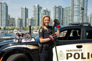 Meghan Agosta in her police uniform and wearing her hockey gloves.