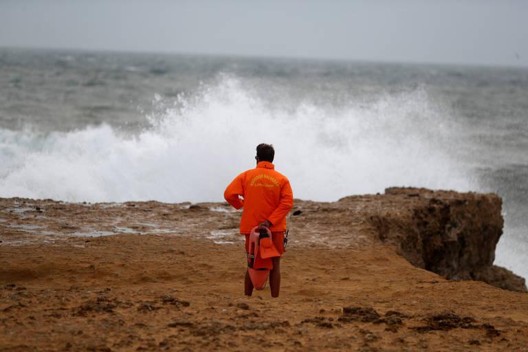 Salva-vidas usa roupa laranja com indicações em amarelo olha de cima de uma ponta as ondas baterem nas pedras