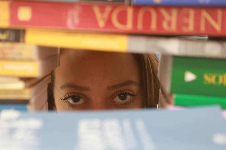 Aluna vítima de violência doméstica posa na biblioteca da Escola Estadual Haroldo Veloso, em Guarulhos (Grande SP)