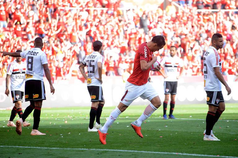 Leandro Damião aponta para o escudo do Internacional após marcar o gol de empate contra o São Paulo