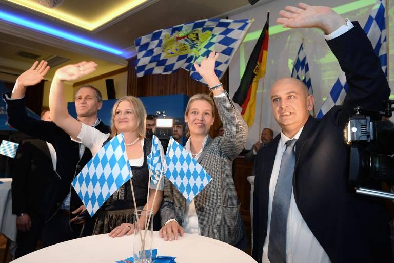 Os três estão sentados à mesa, com as mãos levantadas. Há bandeiras quadriculadas azuis e brancas na mesa e atrás deles