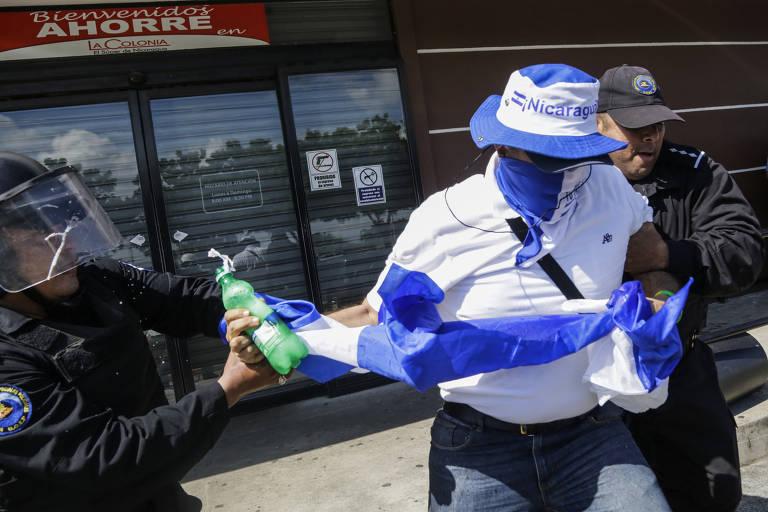 Manifestante vestido as cores da bandeira da Nicarágua é puxado por policial