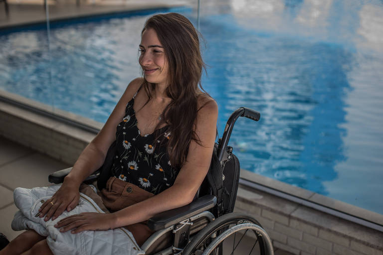 Sentada na cadeira de rodas, Lais Souza à beira da piscina do condomínio em que mora atualmente, em Vila Velha