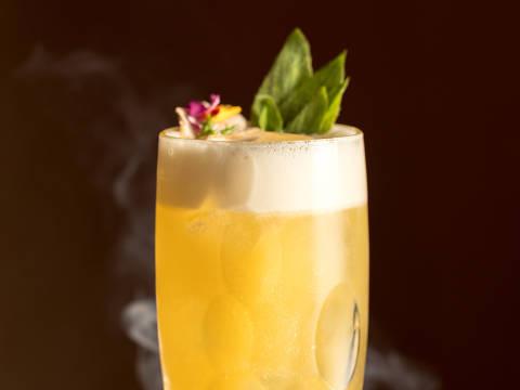 Drinque Zillis' Cocktail, com base de cachaça envelhecida e decorado com flores