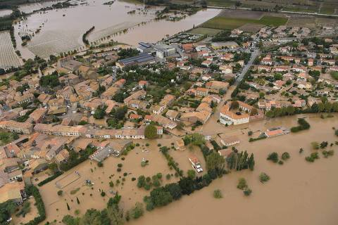 An aerial view taken on October 15, 2018 shows a flooded street in the city of Puichéric, near Carcassone, southern France. - Thirteen people have died after severe storms caused flash flooding across wide stretches of southwest France overnight, sweeping away vehicles and swamping homes, the interior ministry's rescue service said. (Photo by SYLVAIN THOMAS / AFP) ORG XMIT: 1678
