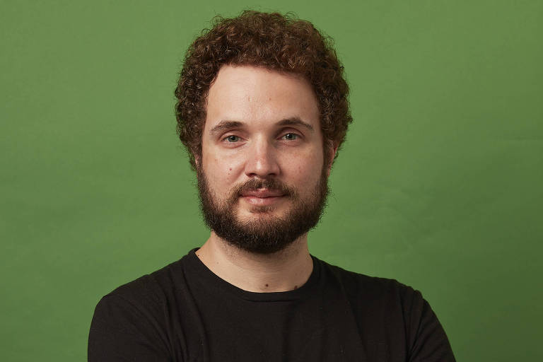 Leandro Beguoci, de braços cruzados e camiseta preta, em frente a uma parede branca, olhando diretamente para a câmera