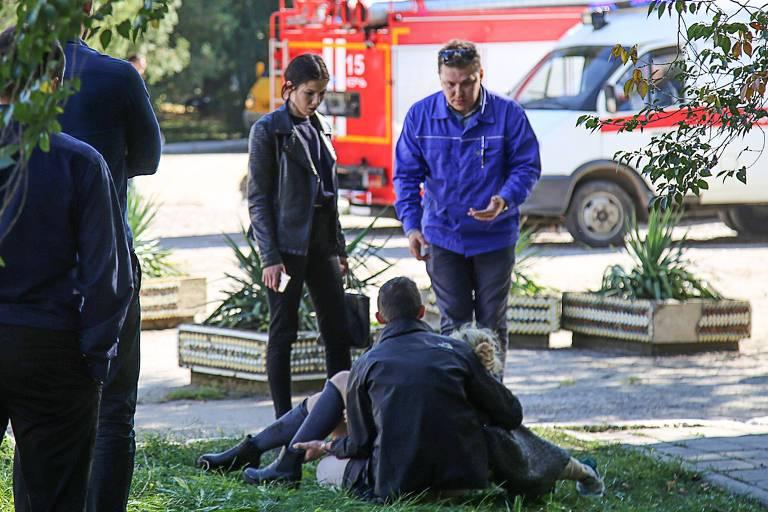 Socorrista carrega uma pessoa ferida no ataque à escola em Kerch, na Crimeia