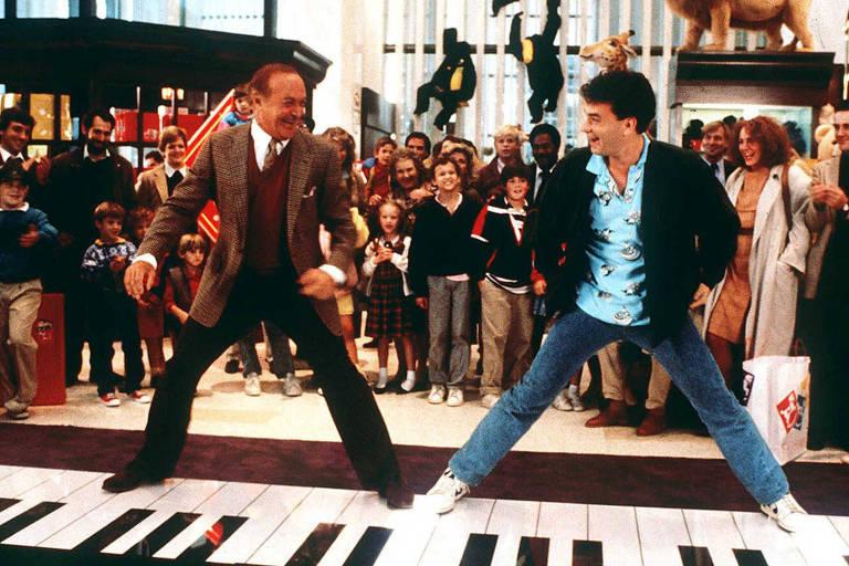 Homens brincam em piano gigante em loja de brinquedos