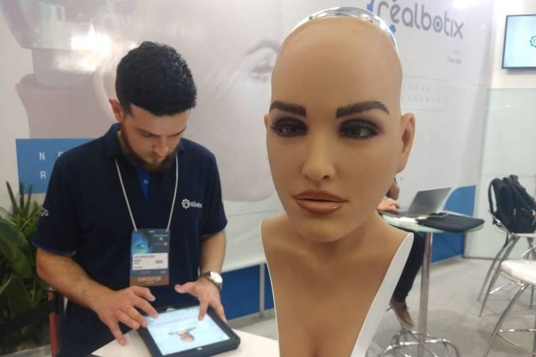 robô tem o rosto de uma mulher. Com cílios falsos, olhos e lábios maquiados. Ela tem pescoço e colo, que simula um decote