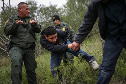 U.S. Border Patrol Agents help men from Central America pass through a barbed wire fence after they were apprehended for illegally crossing into the United States from Mexico in La Joya, Texas, U.S., October 17, 2018. REUTERS/Adrees Latif ORG XMIT: FFF-AAL102
