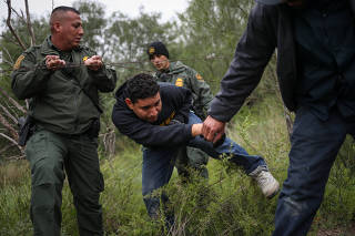 U.S. Border Patrol Agents help men pass through barbed wire fence after they were apprehended for illegally crossing into U.S. from Mexico in La Joya, Texas