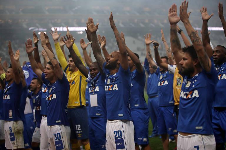 Com os braços erguidos para cima, jogadores do Cruzeiro comemoram a conquista do título da Copa do Brasil