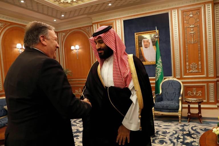 De costas e vestido de terno, Pompeo cumprimenta Mohammed bin Salman, que aparece de frente com a túnica e o adorno de cabeça quadriculado vermelho e branco da realeza saudita. Na parede ao fundo, uma cadeira e um quadro com uma foto do rei Salman.