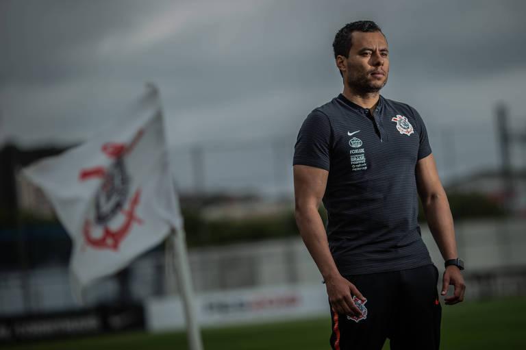 Técnico do Corinthians, Jair Ventura, posa para foto no CT Joaquim Grava, com bandeira do Corinthians tremulando ao lado.