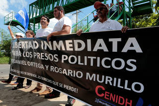 Members of the Nicaraguan Human Rights Center (CENIDH) hold a banner that reads
