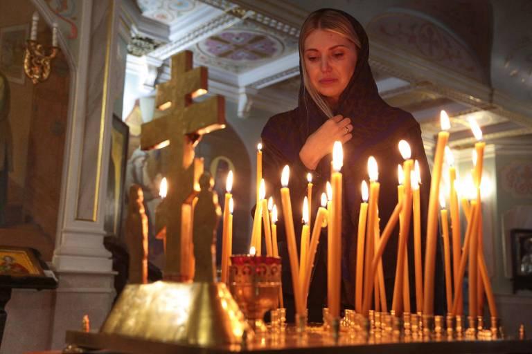 Mulher chora durante cerimônia religiosa em homenagem às vítimas do massacre de Kerch, na Crimeia