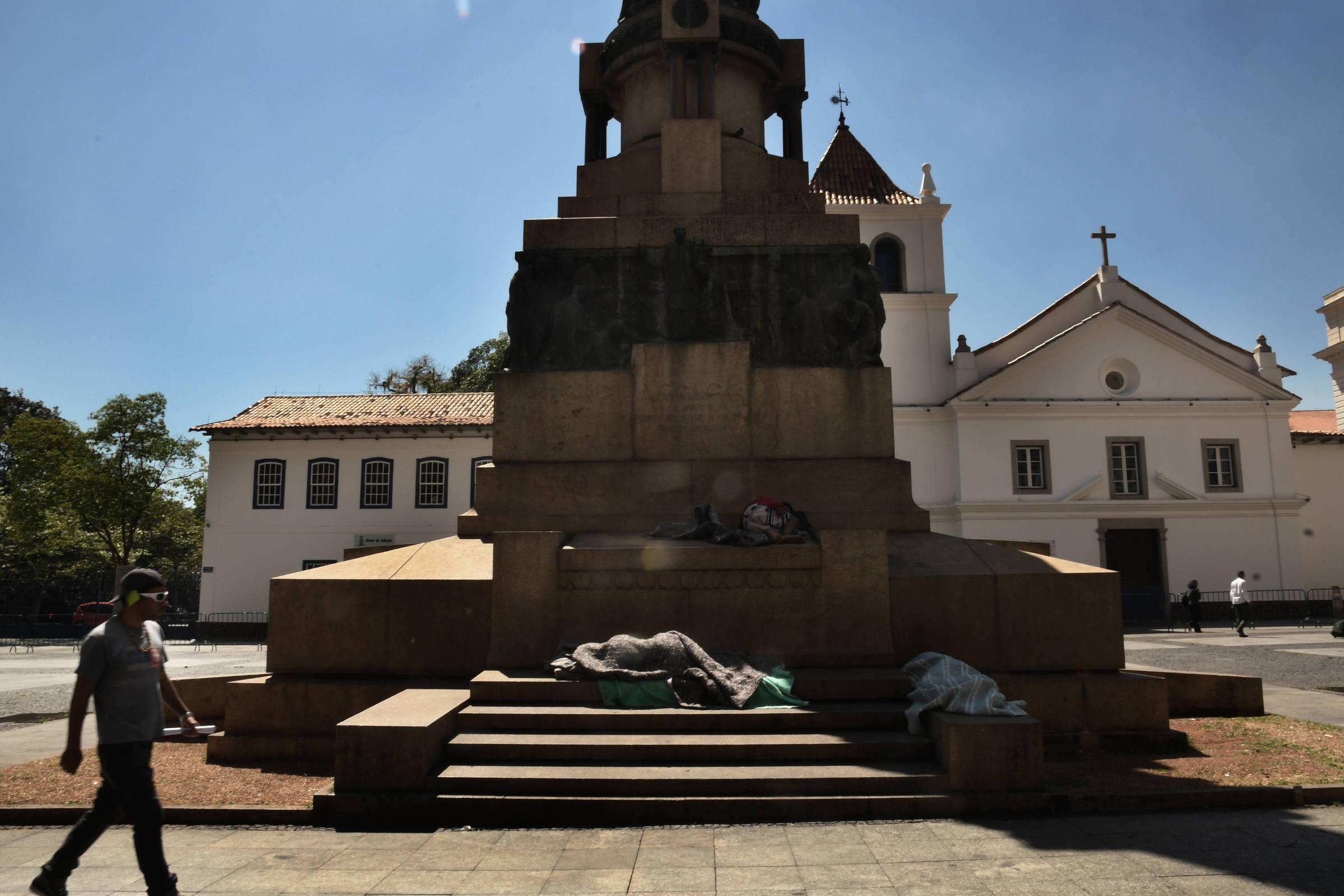 Joelma dorme sob um cobertor nos degraus de um monumento do Pátio do Colégio, no sol