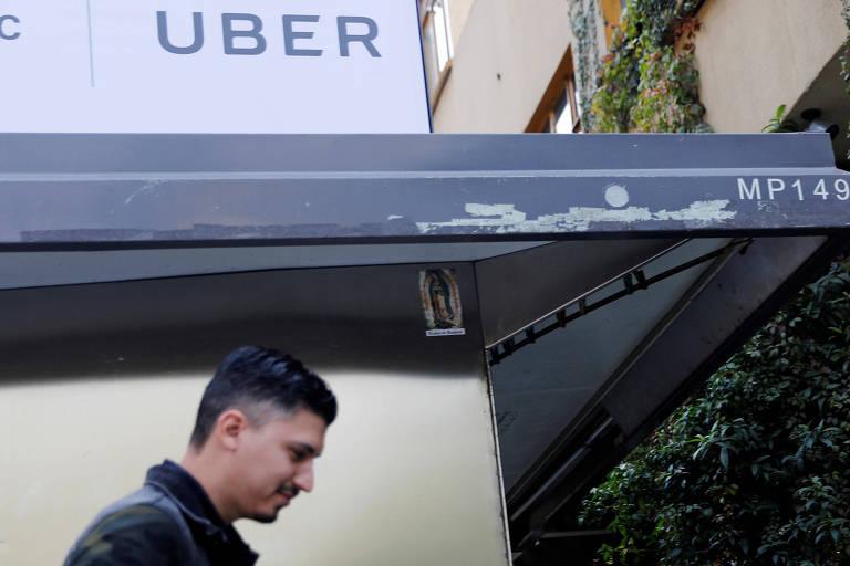 Homem passa à frente de logo da Uber na cidade do México