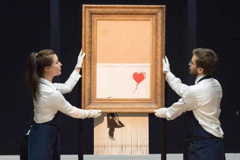Uma mulher e um homem seguram moldura da qual sai a pintura de Banksy, já parcialmente picotada