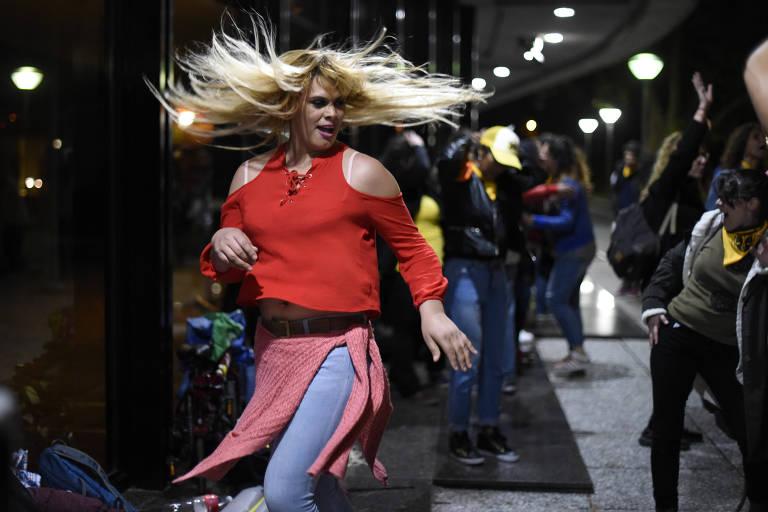 Vestida com calça jeans e camisa vermelha, mulher trans dança na entrada do Congresso. Seus cabelos loiros voam enquanto se movimenta.
