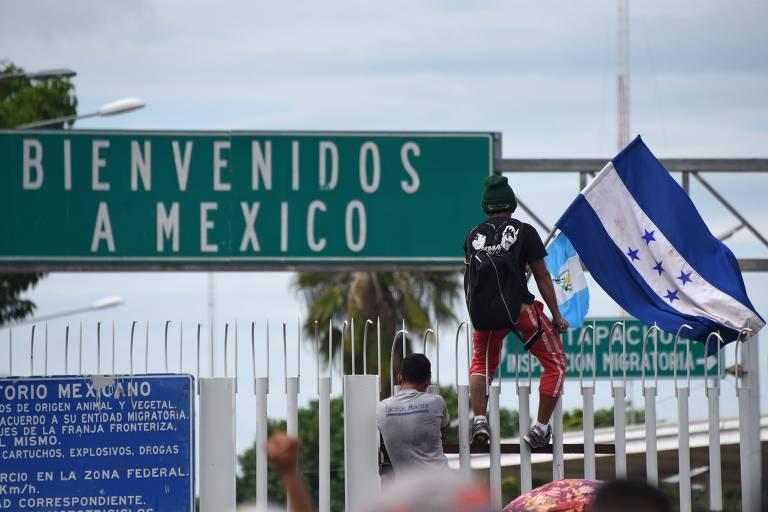 Homem de camisa preta e calça vermelha segura uma bandeira de Honduras em cima de uma grade. Ao fundo, uma placa diz, em espanhol, bem-vindos ao México.
