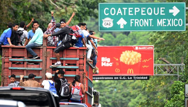 Grupo de cerca de 20 pessoas se agarra nas grades de um caminhão