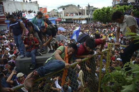 Thousands of Honduran migrants rush across the border towards Mexico, in Tecun Uman, Guatemala, Friday, Oct. 19, 2018. Migrants broke down the gates at the border crossing and began streaming toward a bridge into Mexico. After arriving at the tall, yellow metal fence some clambered atop it and on U.S.-donated military jeeps. Young men began violently tugging on the barrier and finally succeeded in tearing it down. (AP Photo/Oliver de Ros) ORG XMIT: XLAT131