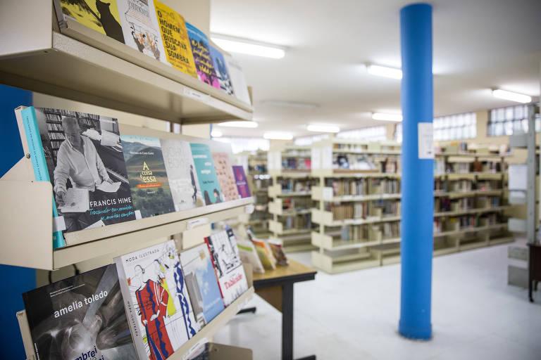 em primeiro plano, estante com livros colocados com suas capas viradas para frente. ao fundo, estantes comuns, onde só é possível ver as lombadas dos livros