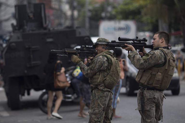 Soldados apontam armas durante operação no complexo do Alemão, no Rio de Janeiro