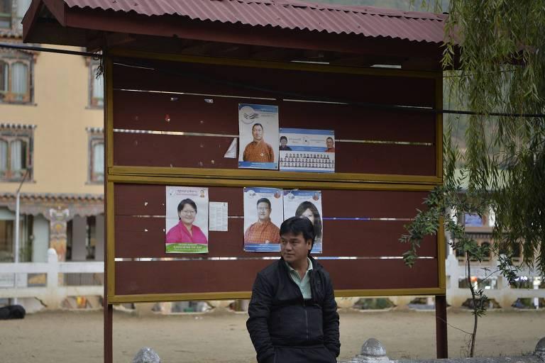 Butanês perto de cartazes eleitorais