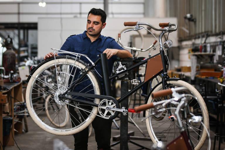 Victor Hugo Cruz, em pé atrás de uma bicicleta, mexe na roda traseira